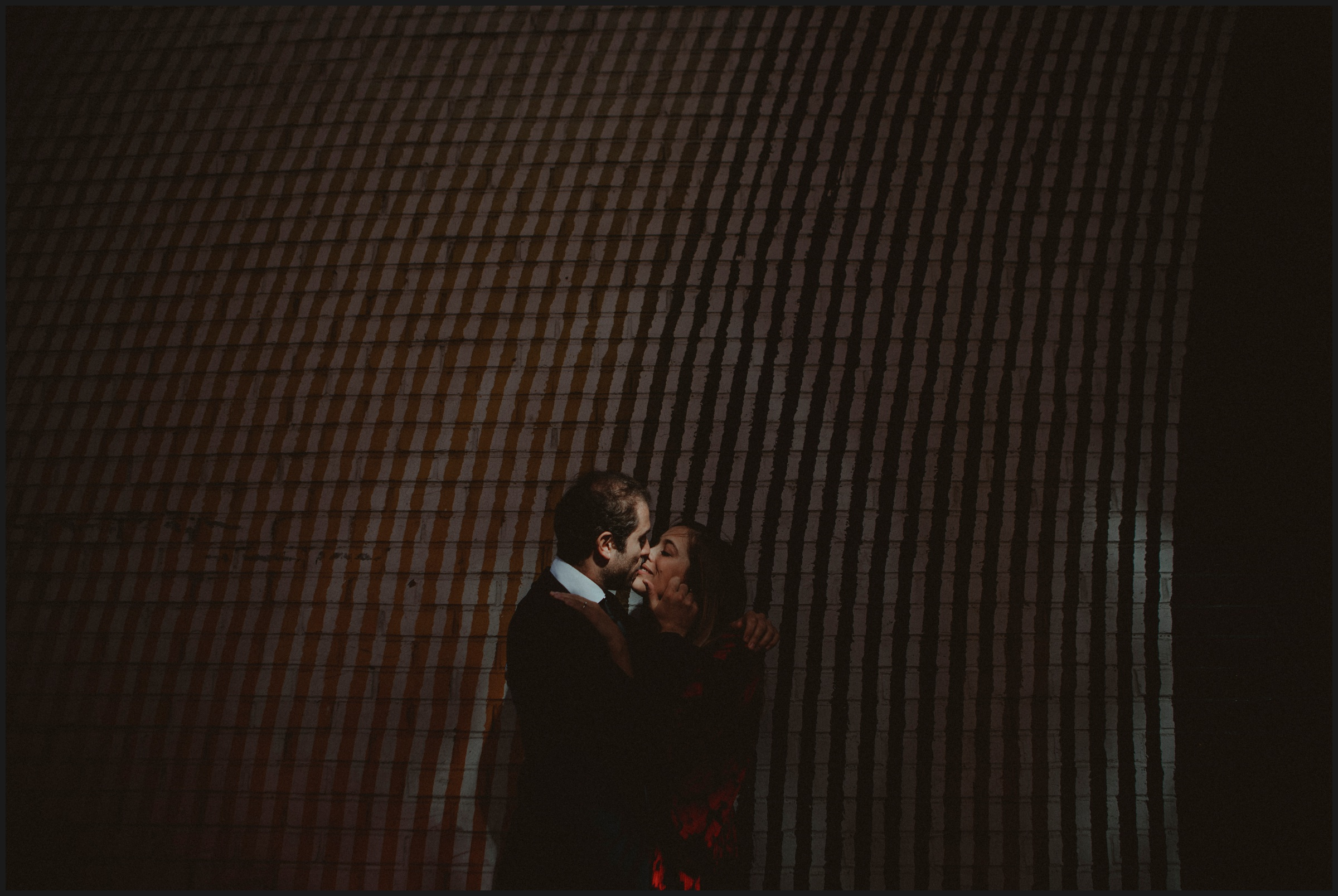 kiss in front of a street art of Brooklyn